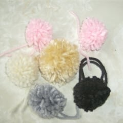 Pom poms made from yarn laying on a table, ready to be attached to your project of choice.