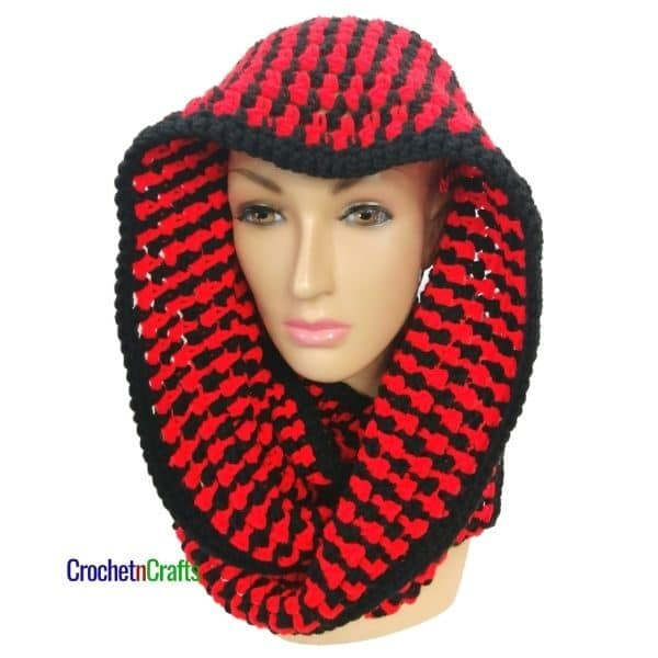 A two tone infinity crochet scarf shown wrapped around the head for a hooded cowl.