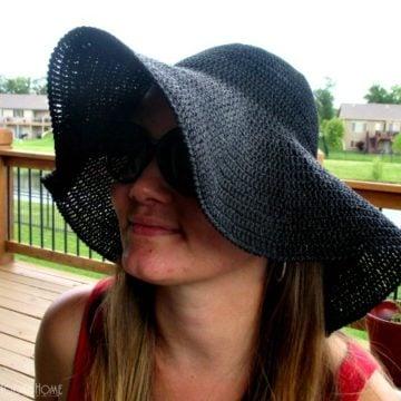 Woman modeling a black floppy sun hat.