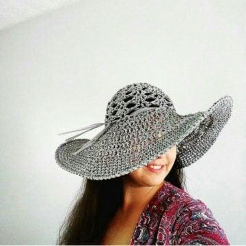 A Grey Crochet Sun Hat modeled on a woman.