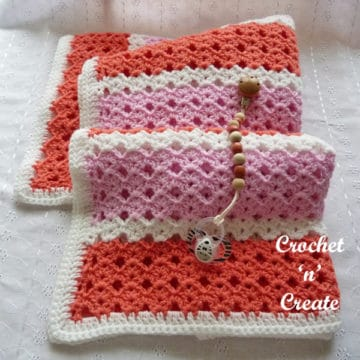 Crocheted baby blanket shown in a striped shell stitch.