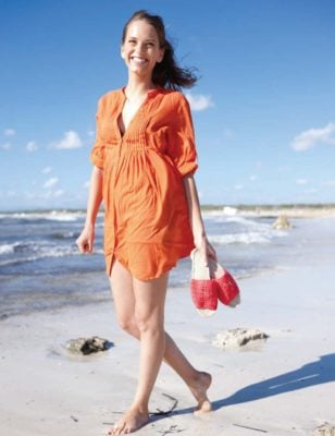 Woman carrying a pair of sandals while walking on the beach.