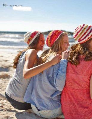 Three women wearing colorful crocheted summer hats.