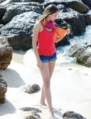 Woman on the beach wearing a light and airy summer scarf.
