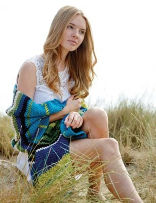 Woman sitting in a grassy area wearing a crocheted stole.