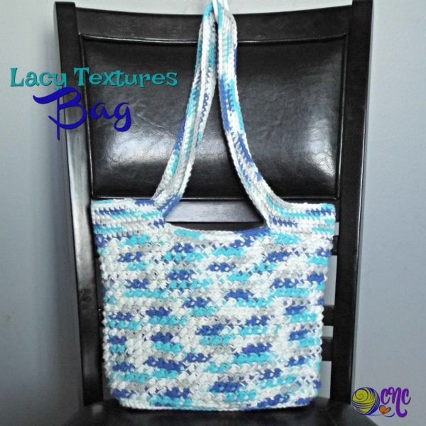 A textured crochet bag pattern worked up in a variegated cotton yarn sits on a chair.