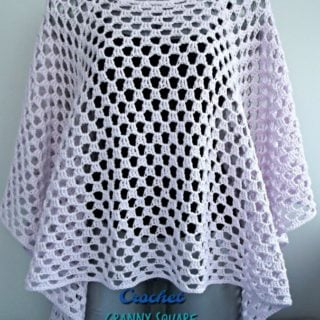 A crocheted granny square poncho draped over a mannequin.