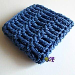 A folded crocheted dishcloth crocheted in a cotton yarn.