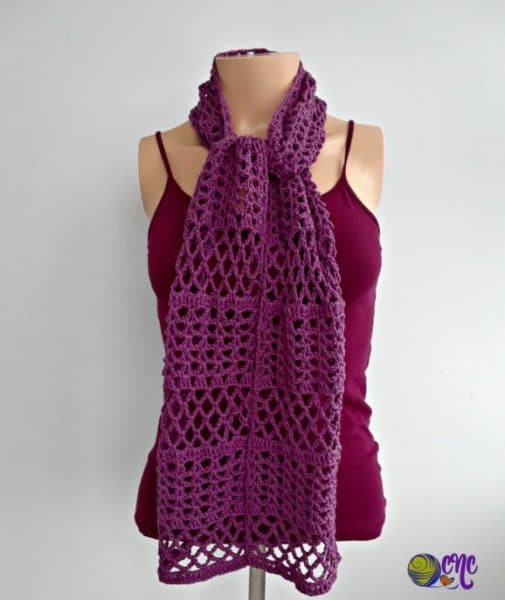 A lacy summer scarf tied in a knot around a mannequins neck. The crochet scarf can be worn in other ways as you like.