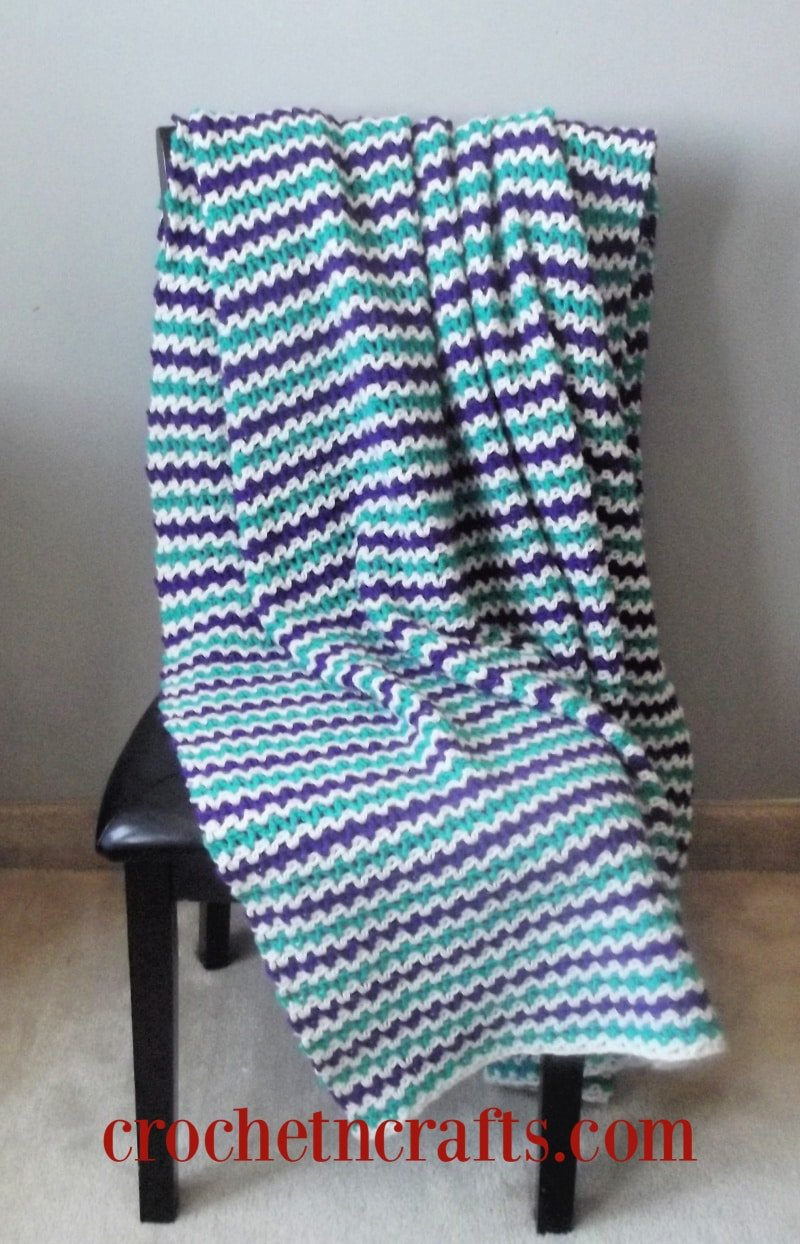 Free v-stitch blanket crochet pattern. The crochet blanket is easy to adjust in size and can be crocheted in any colors.