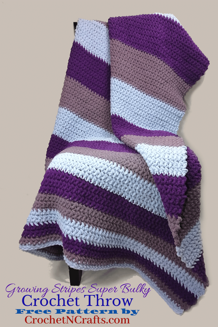 A super bulky crochet throw is draped over a chair. The throw is worked in stripes that get bigger with each repeat of the color.