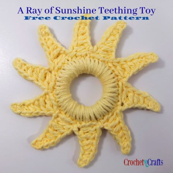 A Ray of Sunshine Teething Toy made with a wooden ring and cotton yarn.