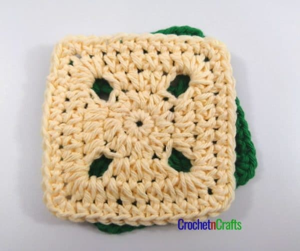 Crochet square coasters shown in yellow and green.