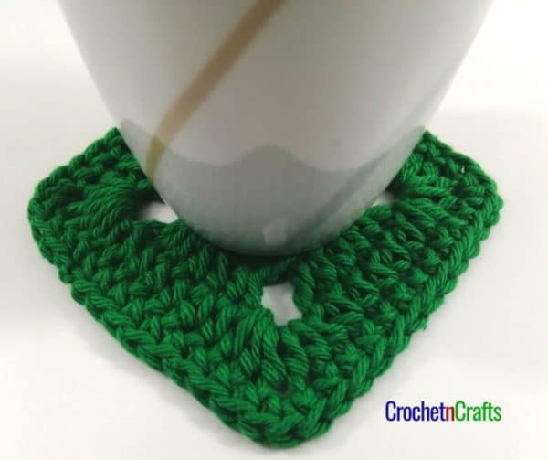 Cup shown on a square green crocheted coaster.