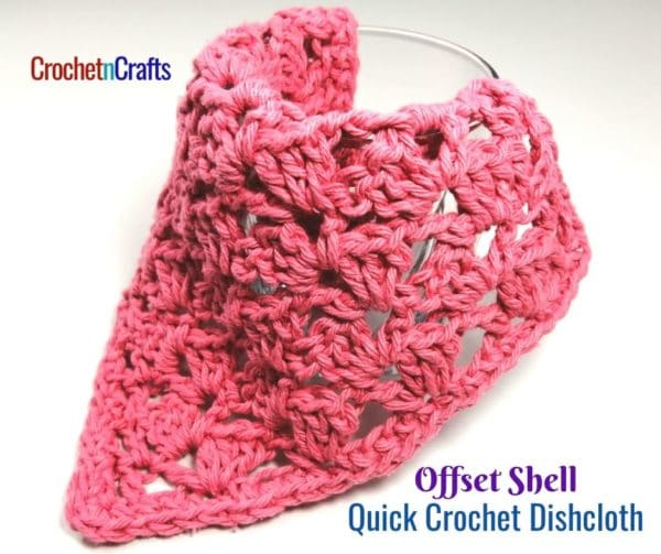 An offset shell crochet dishcloth draped over a glass.