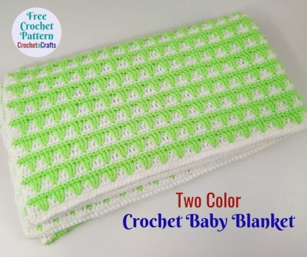 A baby blanket worked up in a white and green yarn neatly folded up.
