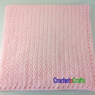 A crocheted baby blanket folded up.