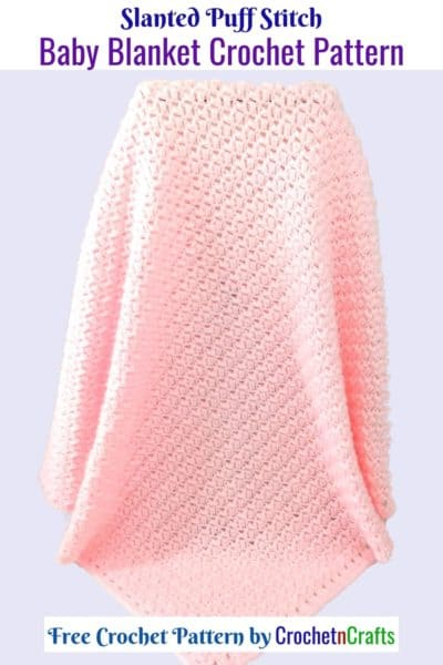 A pink crocheted baby blanket draping down.