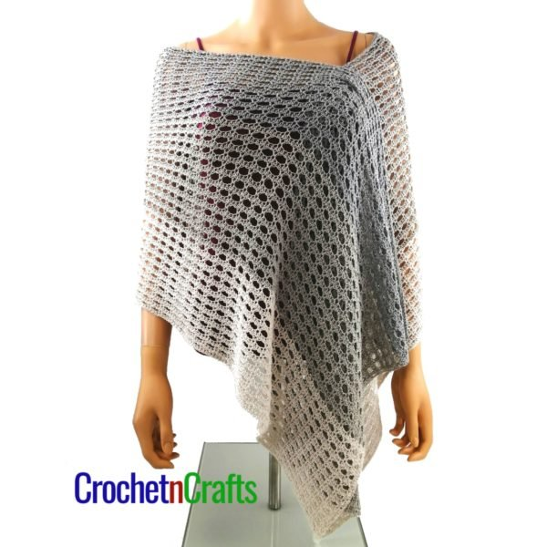 A light and lacy crochet wrap modeled on a mannequin.