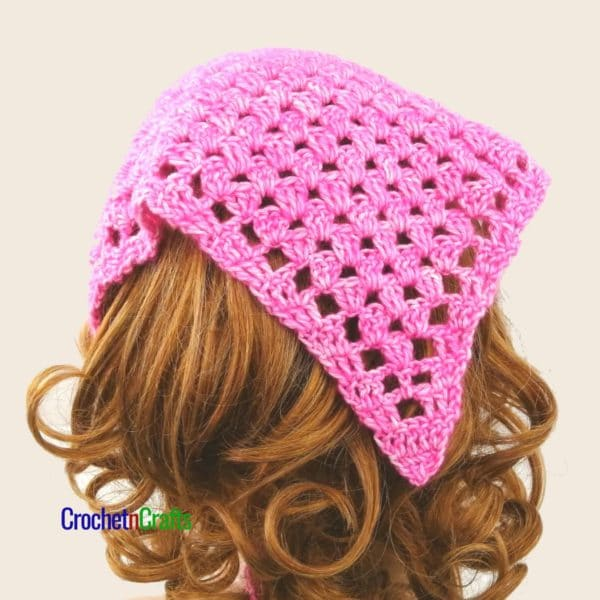 A granny stitch crocheted kerchief shown from the back of the head.