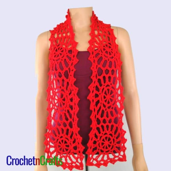 A lacy motif scarf crocheted up in red and modeled on a mannequin.