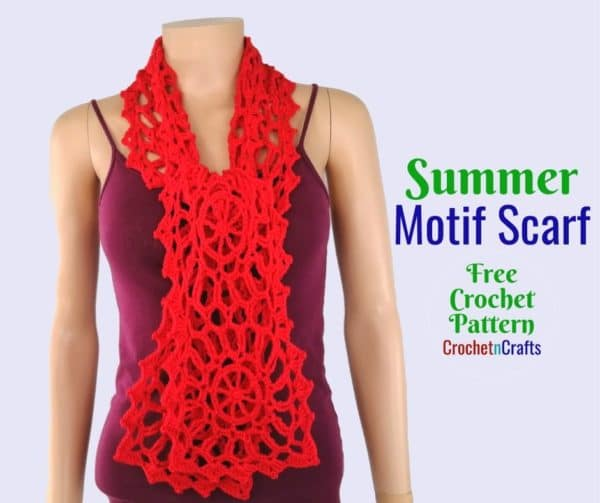 A motif scarf tied in a knot and modeled on a mannequin.