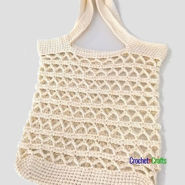 A simple laced crochet tote laid flat.