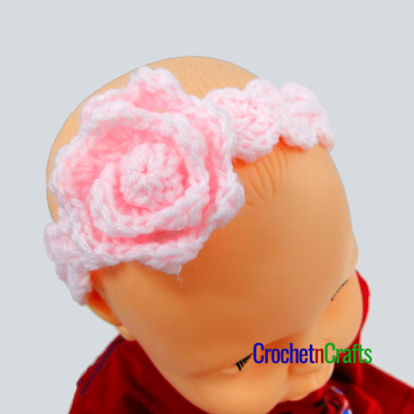 Pink baby headband crochet pattern with a flower.