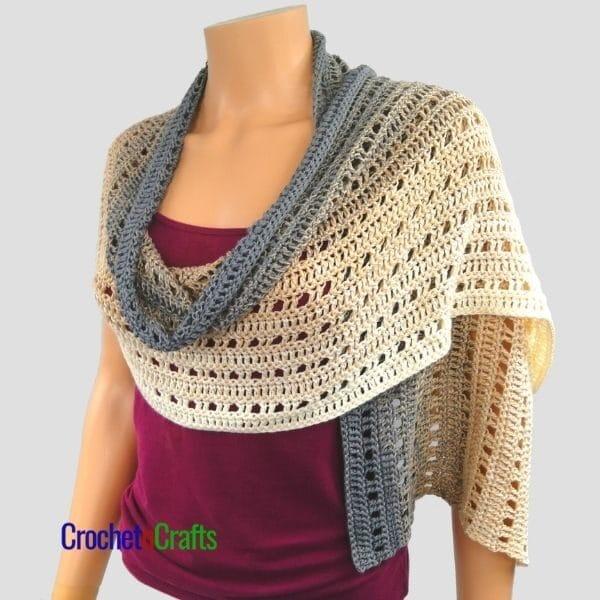 A lightweight easy rectangular crochet shawl draped around the shoulders.