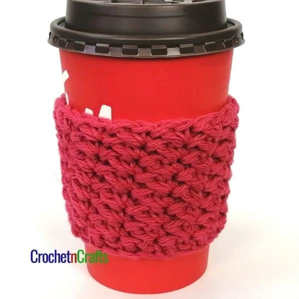 A crocheted cup sleeve shown on a medium-sized take-out coffee cup.