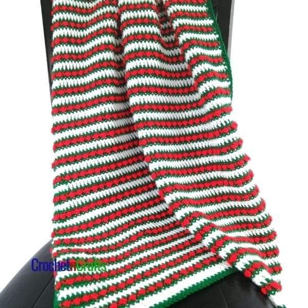 A striped Christmas blanket draped over a chair.