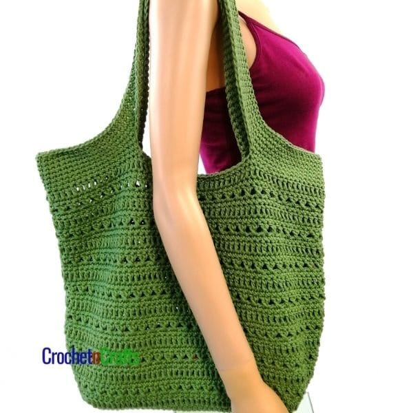 A simple crochet tote hung over a shoulder.