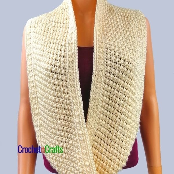 A beautifully textured crochet cowl worn long around the neck.