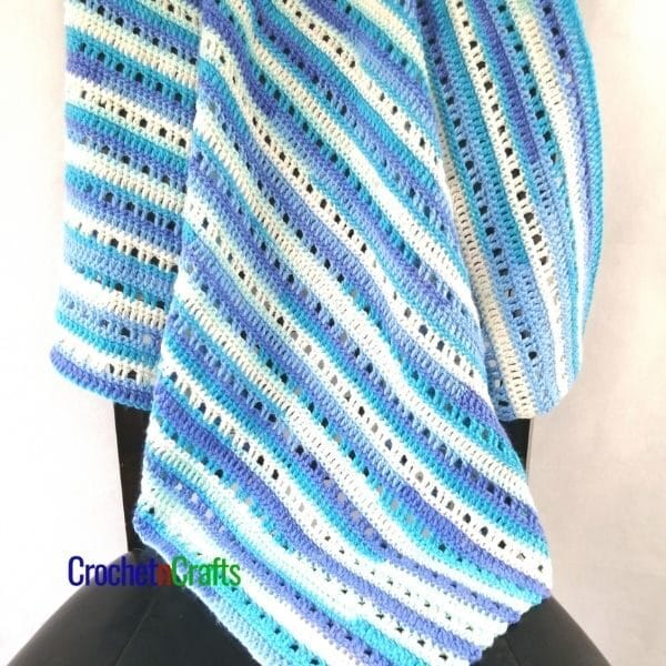 An easy baby blanket crocheted up in a self striping yarn draped over a chair.