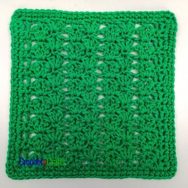 A crochet dishcloth worked up in a clustered v-stitch pattern using a single color of cotton yarn.
