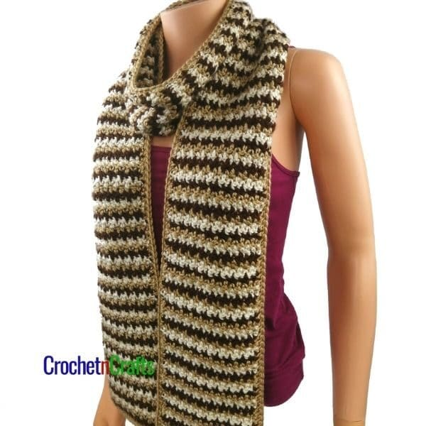 A long and narrow crochet scarf wrapped around the neck for a cozy winter scarf. The scarf is shown in three colors that are changed after each row.