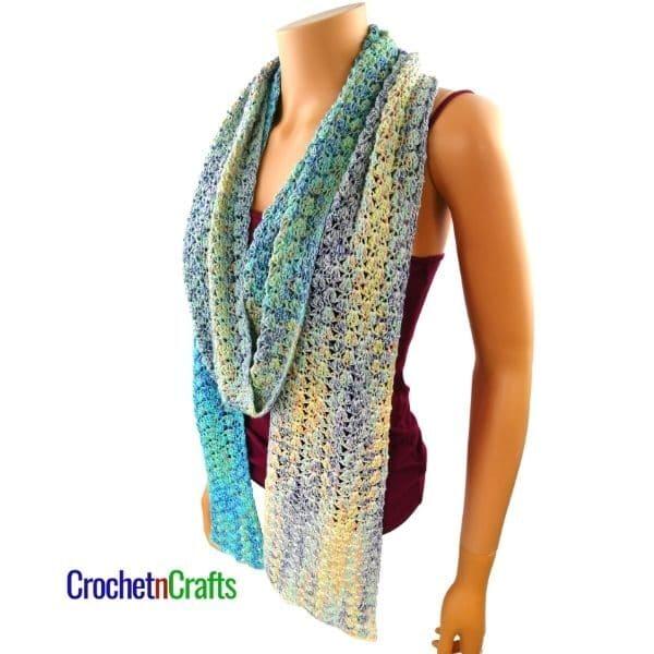 A lightweight crochet spring scarf worn loose around the neck.