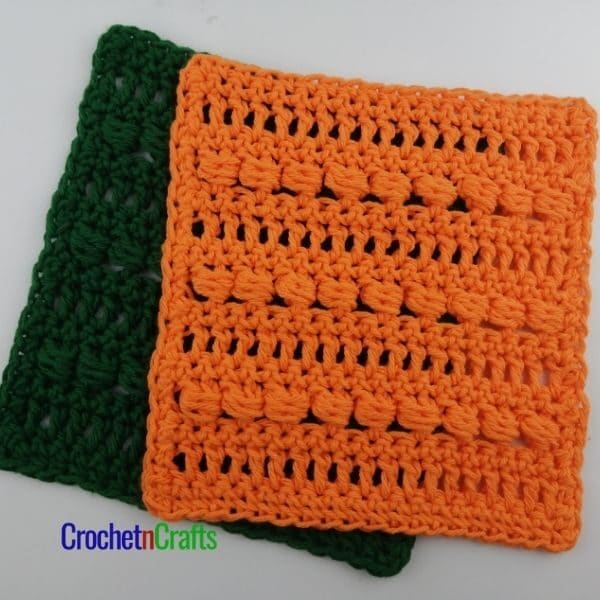 An orange and a green dishcloth shown worked up in the slanted cluster crochet stitch.