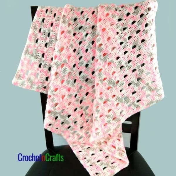 A crochet baby blanket is draped over the back of a chair. It's a simple lace pattern shown in a variegated yarn with pinks, gray and white.
