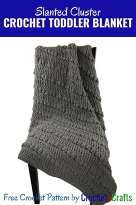 The slanted cluster crochet lapghan or toddler blanket draped over a chair.