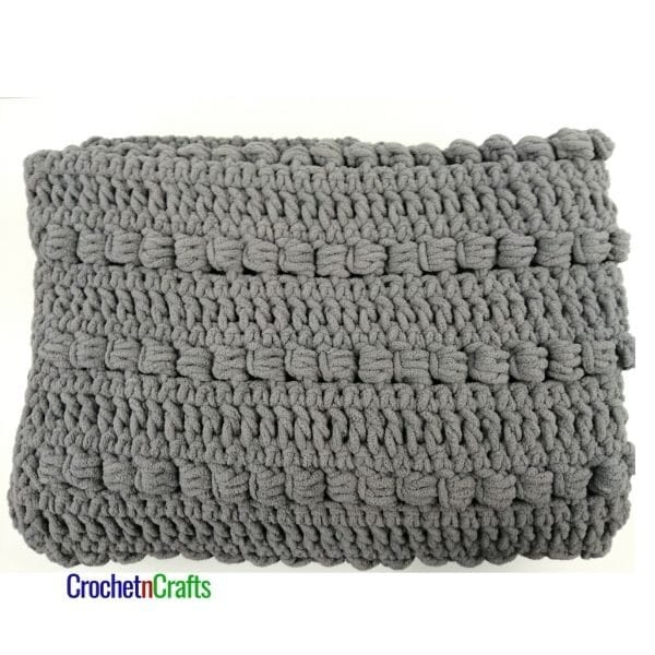 A crochet blanket shown folded up. The blanket is crocheted in the slanted cluster stitch using a super bulky yarn.