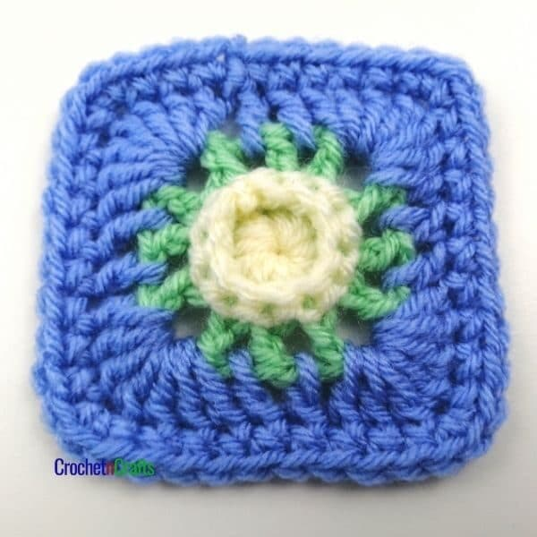 A small afghan square shown in three colors, with a flower-like center.