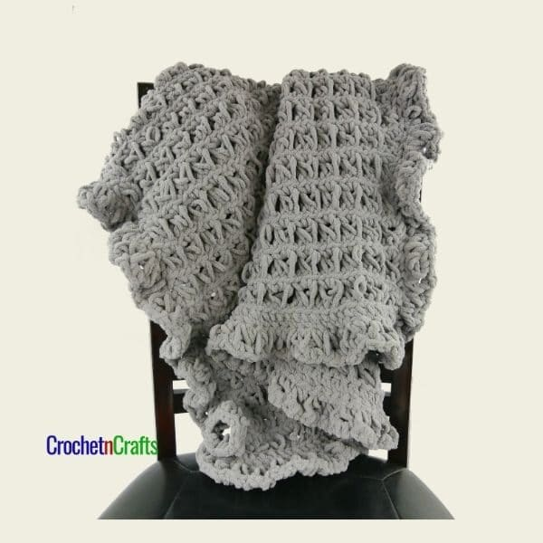This broomstick lace blanket is worked up in a gray for a boy. It has a nice ruffled edge.