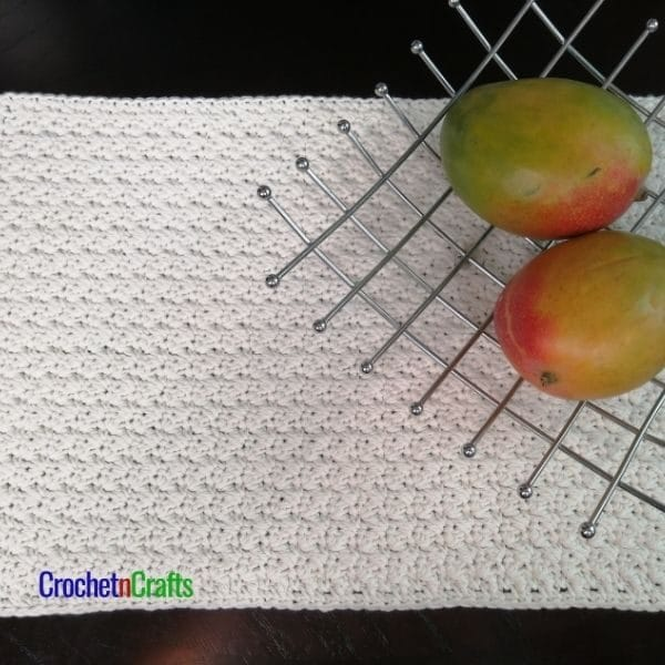 A textured placemat shown with a fruit basket.