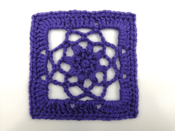 A floral laced afghan square shown in purple.