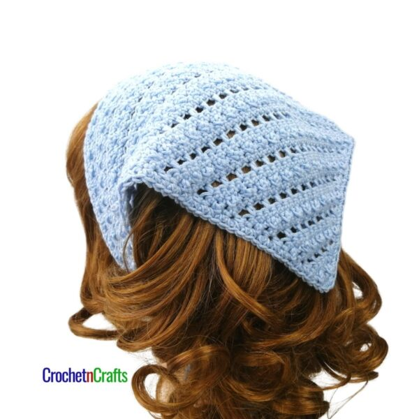 A textured and open stitch crochet kerchief shown from the back of the head.