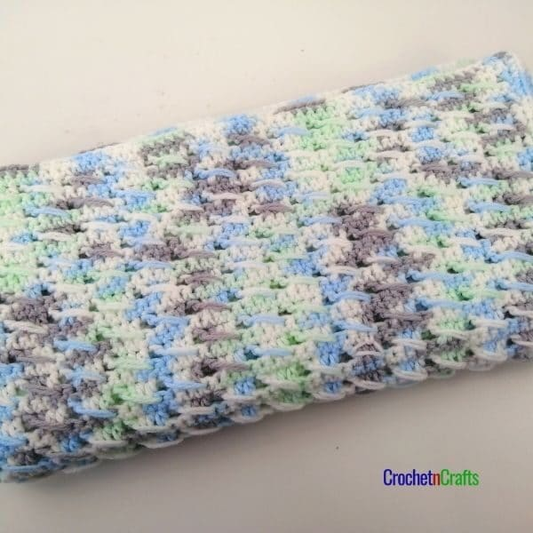 A textured baby blanket shown folded up.
