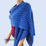 An open stitch cotton and rectangular shawl draped over the shoulders.