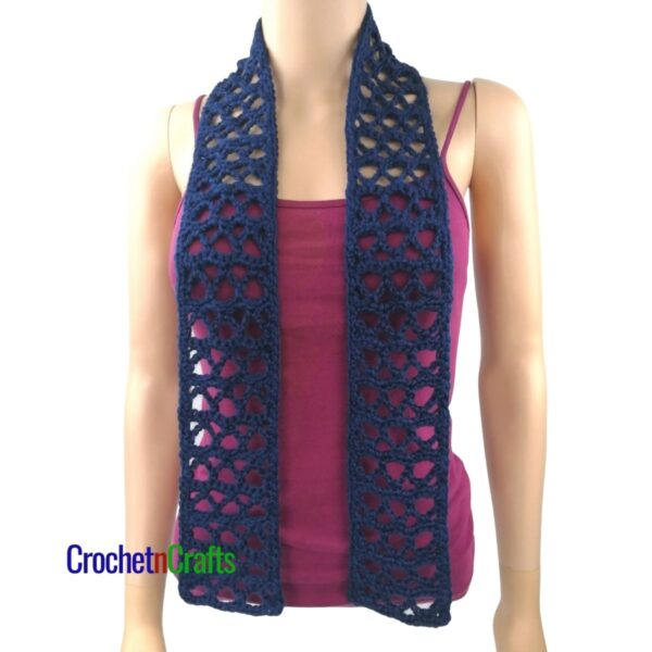 An open stitch scarf draped over the shoulders.
