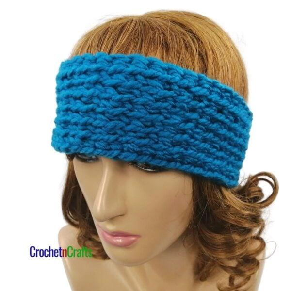 Chunky crochet ear warmer worn on adult small.